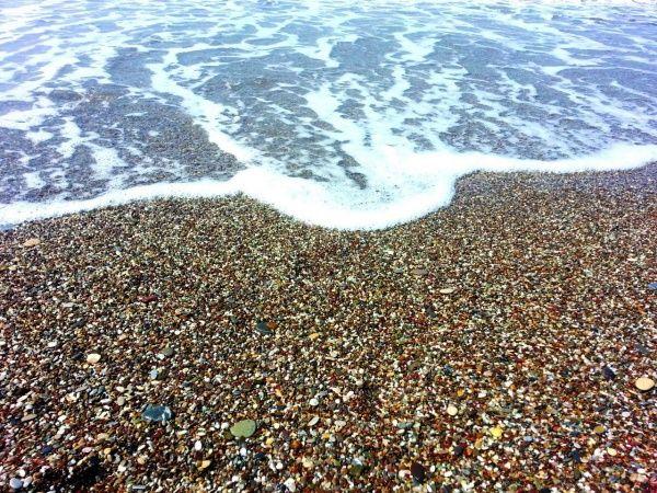 Цветной галечный пляж Клеопатры на курорте Сиде в Турции