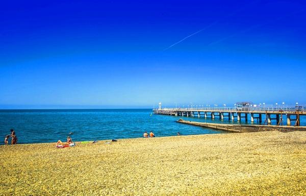 Галечный пляж черного моря и длинный причал
