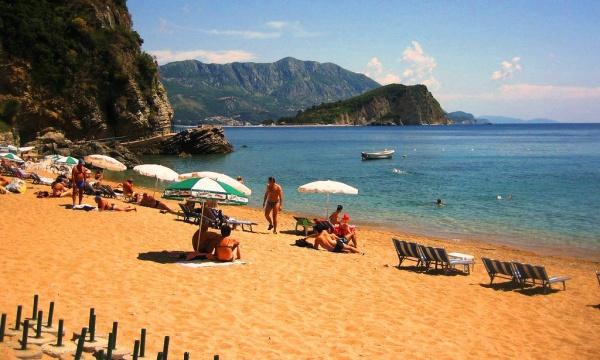 Пляж у залива, скалистые горы, зонты и шезлонги на курортах Черногории